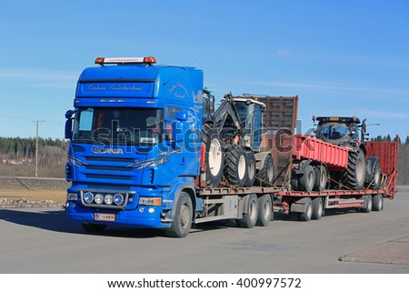 FORSSA, FINLAND - APRIL 2, 2016: Blue Scania R500 truck transports agricultural tractors and equipment on trailer at spring in South of Finland.  - stock photo
