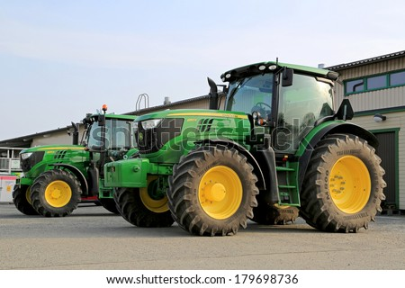 FORSSA, FINLAND - MARCH 1, 2014: John Deere 6150R and 6125M agricultural tractors on display. Two John Deere innovations have won awards at the 2014 FIMA show held in Zaragoza, Spain in February. - stock photo