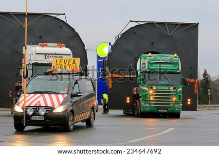 FORSSA, FINLAND - NOVEMBER 30, 2014: Pilot car and two trucks with oversize loads. One pilot vehicle with height measuring pole is required, if the load exceeds 5 m in height. - stock photo