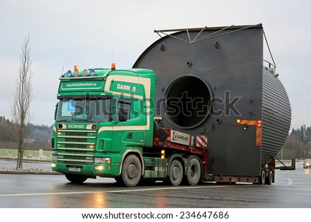 FORSSA, FINLAND - NOVEMBER 30, 2014: Scania 124L truck hauls a wide load. On Finnish roads at least one escort vehicle is necessary, if the load exceeds 3,5 m in width. - stock photo