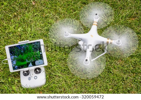 FORT COLLINS, CO, USA - AUGUST 28, 2015:  Spinning propellers and getting ready to take off. DJI Phantom 3 hexacopter drone with radio controller and iPad Air on grass area. - stock photo