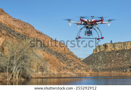 FORT COLLINS, CO, USA, February 18,  2015:  F550 Flame Wheel  hexacopter drone is  flying with a camera over mountain lake - stock photo
