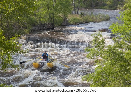 FORT COLLINS, COLORADO, USA - JUNE 4, 2011: White water rafter enjoys springtime snow melt when floating over Mad Dog Rapid on Cache la Poudre River west of Fort Collins. - stock photo