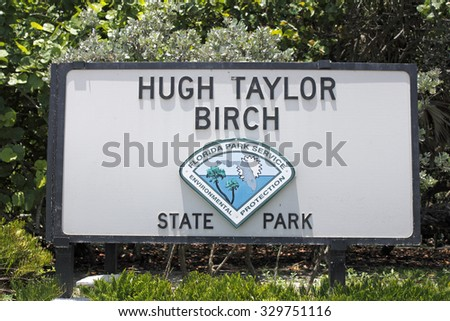 Fort Lauderdale, FL, USA - June 25, 2014: Large rectangle painted wooden Hugh Taylor Birch State Park sign located along  State Route A1A north of Sunrise Boulevard on a sunny day.
