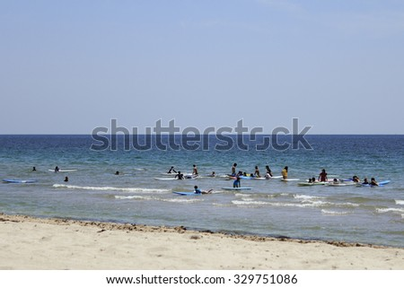 Fort Lauderdale, FL, USA - June 25, 2014: Many children and young adults practice riding surf boards in the Atlantic Ocean beach near Birch State park. The children and teenagers on the beach surf  - stock photo