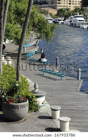 FORT LAUDERDALE, FLORIDA - FEBRUARY 3: Boats moored and people relaxing and walking along the wooden walkway at the Riverwalk beside the New River on February 3, 2013 in Ft Lauderdale, Florida. - stock photo