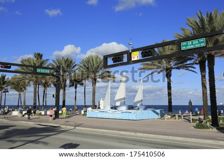 FORT LAUDERDALE, FLORIDA - JANUARY 23, 2014: Three sail boats on a water like pedestal with 3 all white waves on Fort Lauderdale Beach sculpture at corner of Las Olas and A1A on a sunny winter day.  - stock photo