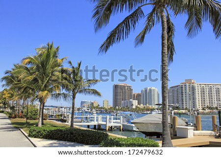 FORT LAUDERDALE, FLORIDA - MARCH 30, 2013: Beautiful view of boats on the Atlantic Intracoastal with modern buildings lining its banks along with tropical palm trees and foliage on a sunny day.  - stock photo
