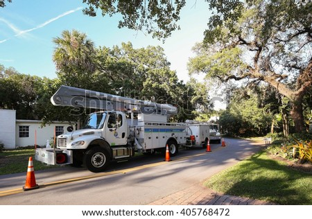 FORT LAUDERDALE, FLORIDA, USA - April 9, 2016:  A team of Florida Power and Light repair trucks parked and working in a neighborhood with abundant vegetation.