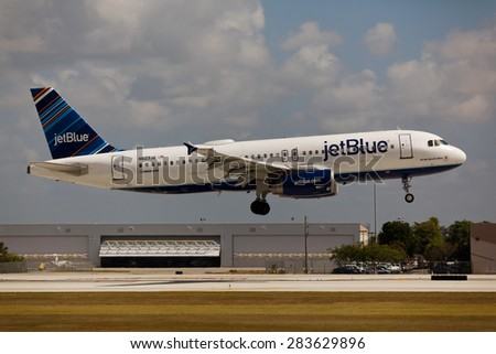FORT LAUDERDALE, USA - JUNE 2, 2015: A JetBlue Airbus A320 landing at the Fort Lauderdale/Hollywood International Airport. JetBlue is a low-cost non-union carrier with its base in New York City. - stock photo