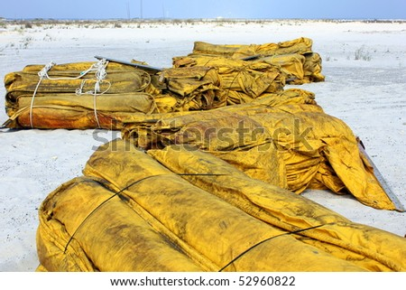 FORT WALTON BEACH, FL - MAY 9: Piles of boom on white sand beach ready to protect the shore from BP oil spill, May 9th, 2010, in Fort Walton Beach, FL. - stock photo