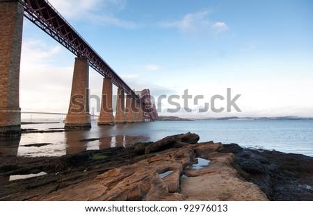 Forth Rail Bridge landscape with foreground rocks - stock photo