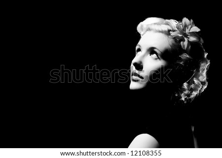 Forties hollywood black and white a beautiful woman stares right out of frame. Minimal lighting and strong contrast copy space to left - stock photo