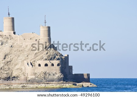 Fortified building on a cliff overlooking the harbour entrance to the palace of the Sultan of Oman. - stock photo