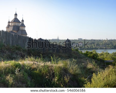 Fortified stockade settlement of Zaporizhzhya guard army troop 16-18 centuries. Panoramic view from Khortytsia island on broad Dnipro in quiet evening summertime sunset with space for text on blue sky
