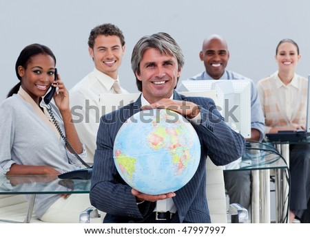Fortunate business team at work showing a terrestrial globe  in the office - stock photo