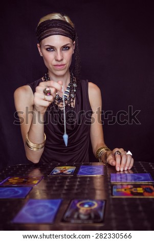 Fortune teller forecasting the future with pendulum on black background - stock photo