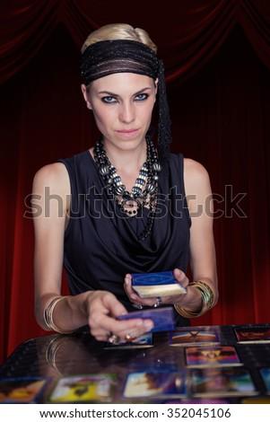 Fortune teller forecasting the future with tarot cards against large hanging curtain - stock photo