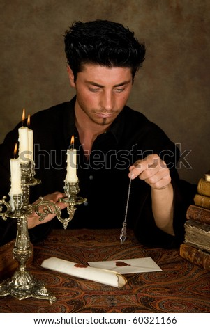 Fortune-teller holding a pendulum aboven vintage letters - stock photo
