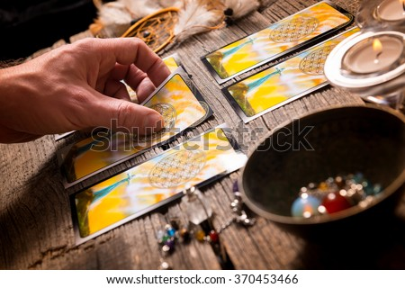 Fortune teller holding a tarot card - stock photo