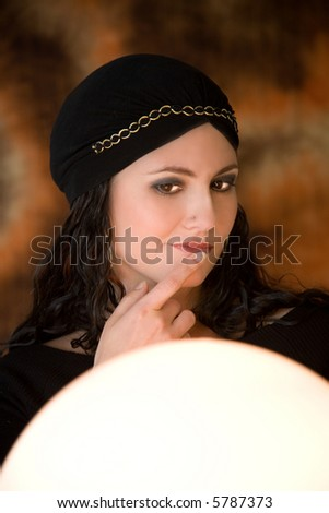 Fortune teller looking a bit doubtful in her crystal ball (stripes in the background is the pattern of the fabric!) - stock photo