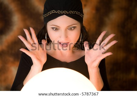 Fortune teller looking very surprised at what she is seeing in her cristal ball - stock photo