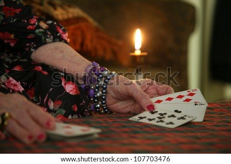 fortune teller's cards with candle light in back - stock photo