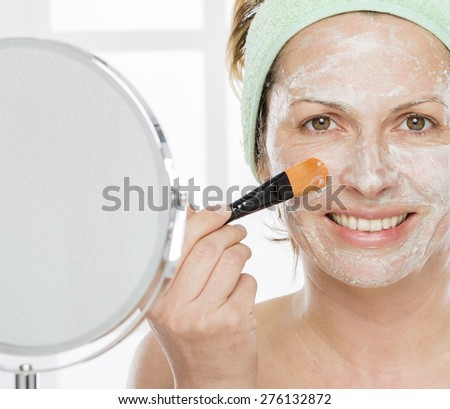 Forty year old woman putting mask on her face - stock photo