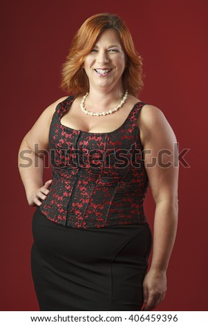 forty year old woman with red hair, wearing a red corset against a red background - stock photo