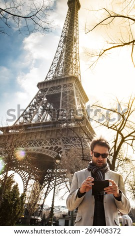 Forty years old caucasian man looking at a mobile phone (smartphone). Eiffel Tower as background. Tourist searching for information about Paris concept. - stock photo