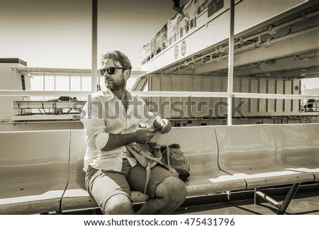Forty years old caucasian tourist man in sunglasses single traveling by ferry boat (ship) with backpack - transportation.