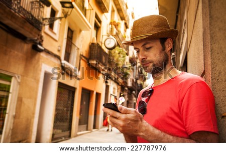 Forty years old caucasian tourist man looking at mobile phone outdoor near old city buildings - summer holiday - stock photo