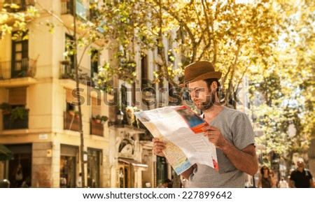 Forty years old caucasian tourist man looking at the city map outdoor among old buildings - summer holiday traveling - stock photo
