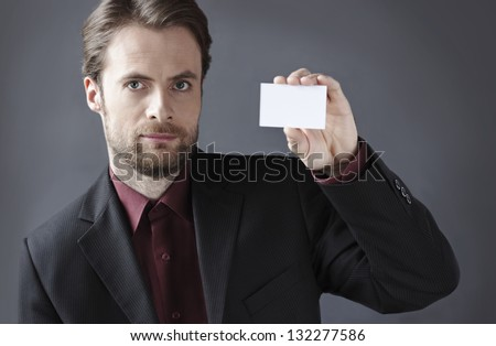 Forty years old serious businessman presenting blank business card on a grey background. Introducing company concept. - stock photo