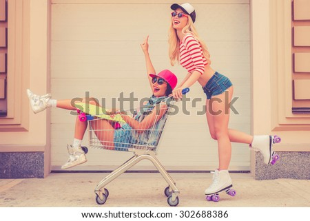 Forward to adventures! Side view of joyful young woman on roller skates carrying her female friend in shopping cart and smiling while skating against the garage door - stock photo