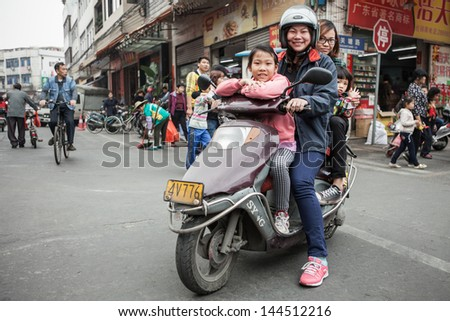 FOSHAN, GUANGDONG/CHINA - MARCH 16: Four unidentified people share the same scooter. Shunde District of Foshan City, Guangdong Province in Southern China on March 16th, 2013.  - stock photo