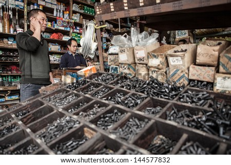 FOSHAN, GUANGDONG/CHINA - MARCH 16: Unidentified man talks on phone while another stands at counter at a hardware store. Shunde District of Foshan City, Guangdong Province, China on March 16th, 2013. - stock photo