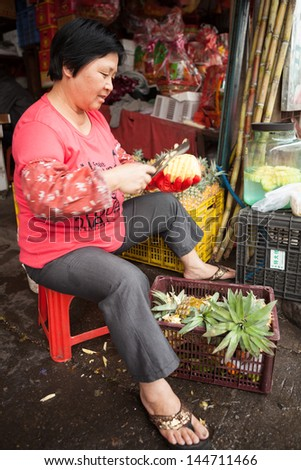 FOSHAN, GUANGDONG/CHINA - MARCH 16: Unidentified street vendor peels pineapples, Shunde District of Foshan City, Guangdong Province in Southern China on March 16th, 2013.