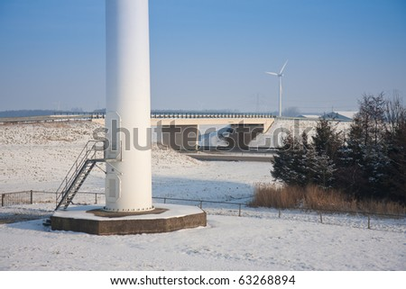 Foundation of a big windmill near a motorway in a snowy landscape of the Netherlands - stock photo