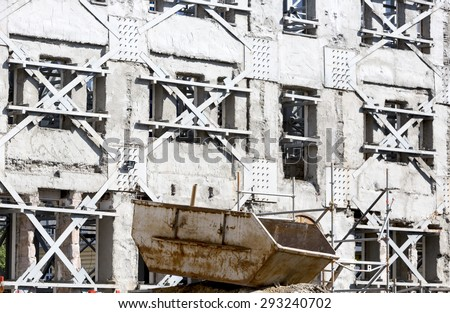 Foundations of collapsed building. One of the walls still standing. - stock photo