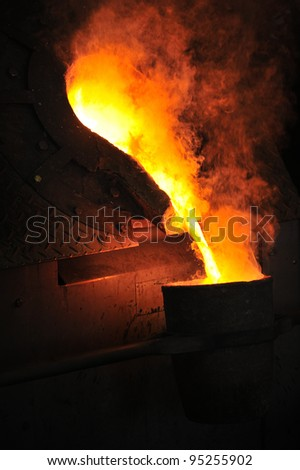 Foundry - molten metal poured from ladle for casting - stock photo