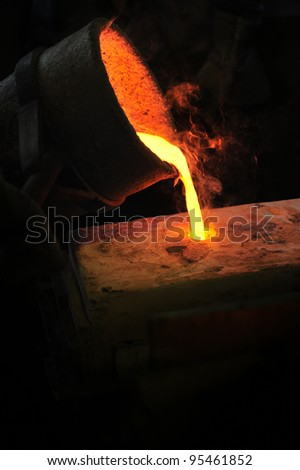 Foundry - molten metal poured from ladle into mould - lost wax casting - stock photo