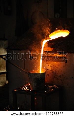 Foundry - Molten metal poured from lathe for casting - stock photo