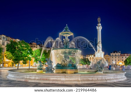 Fountain at night in the center of the city. Romantic Lisbon street with the typical old buildings and new buildings - stock photo