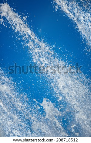 Fountain drops of pure brilliant water against a blue clear sky - stock photo