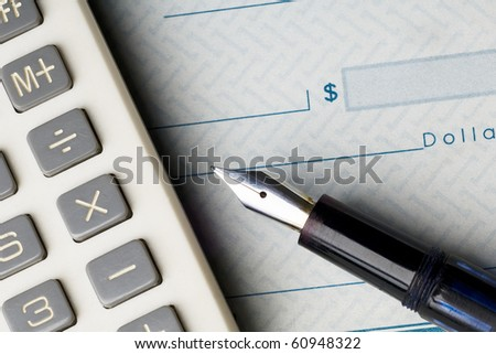 fountain pen and calculator on a blank check - stock photo