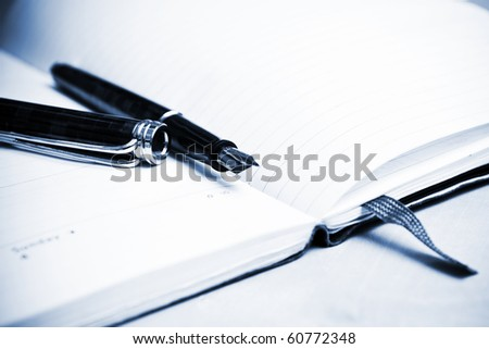 Fountain pen and calendar in composition in blue tone - stock photo