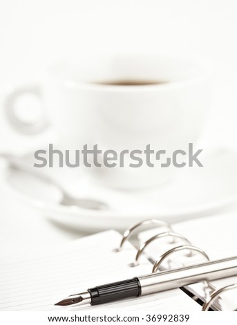 fountain pen and diary with a coffee cup on a background