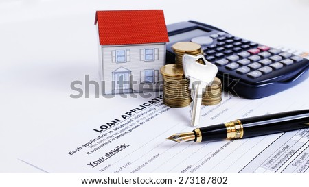 Fountain pen and key and calculator and paper house and coins stack on Loan Application form for Mortgage loans concept - stock photo