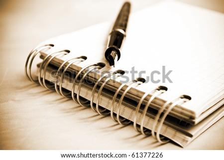 Fountain pen and notebook in composition in sepia tone - stock photo